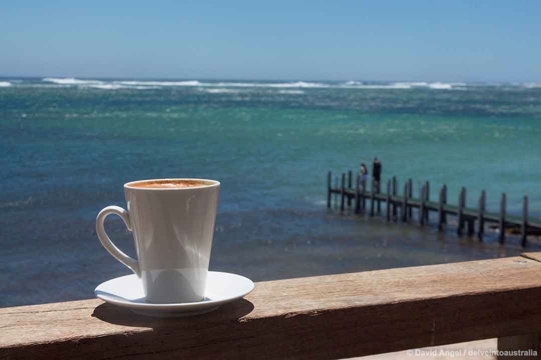 Image of a cup of coffee with Gnarabup Beach and the Indian Ocean in the background